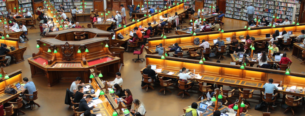 A photo of a large university library, featuring lots of students at work
