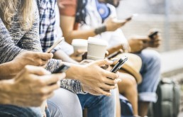 Friends group using smartphone with coffee at university college break