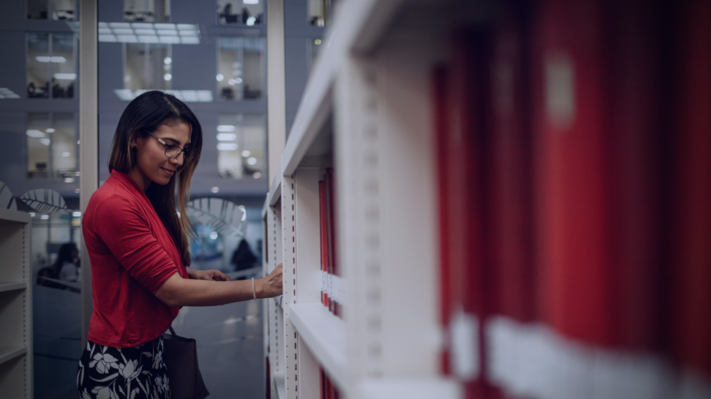 A friendly librarian seeks a book among the stacks