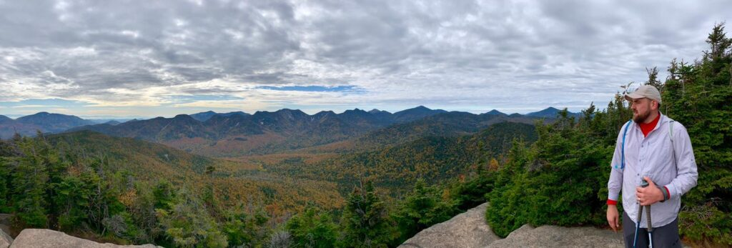 scholcommlab researcher Anton Ninkov looks out at wide view of mountains and trees at Adirondack High Peaks, upstate New York.