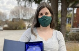 scholcommlab director stefanie haustein holds her new open scholarship award, while wearing a green mask