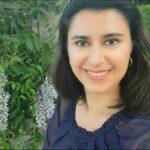 sanam ebrarhimzadeh poses in front of some fresh greenery