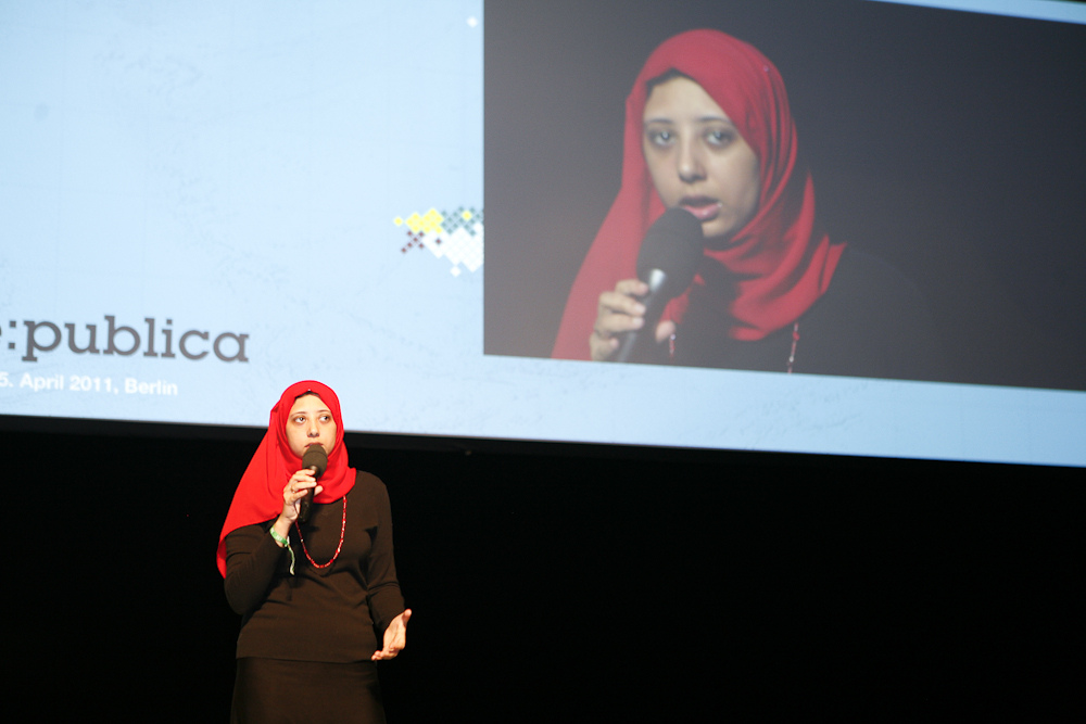 Noha Atef presents a talk on a brightly lit stage