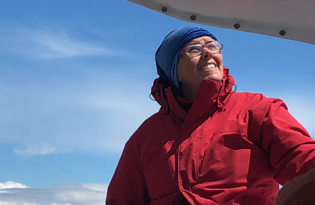 Michelle Riedlinger, in a red jacket, on a sailboat against a bright blue sky.