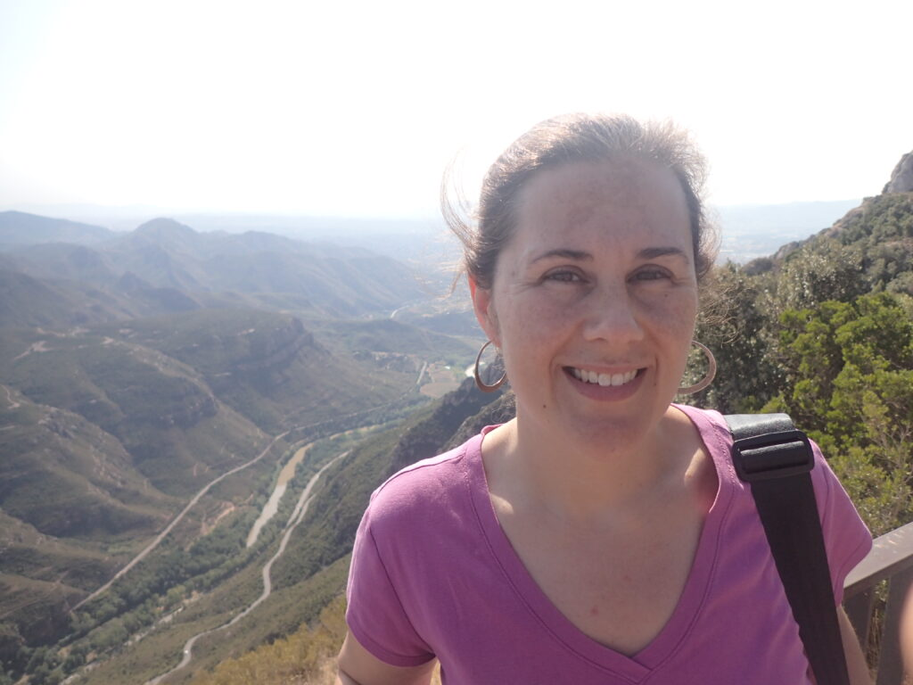 Scholarly Communications Lab member Lauren Maggio smiles for the camera in front of a beautiful view