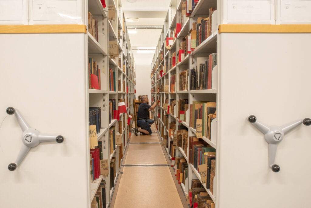 A man crouches down to look for a book on a lower library shelf.