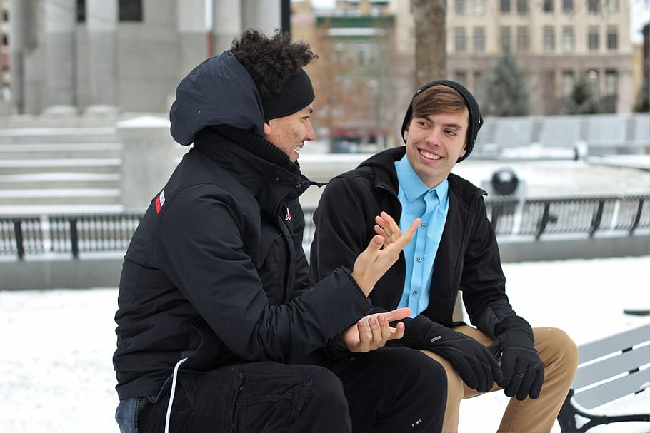Two people talking and connecting on a bench in a snowy city
