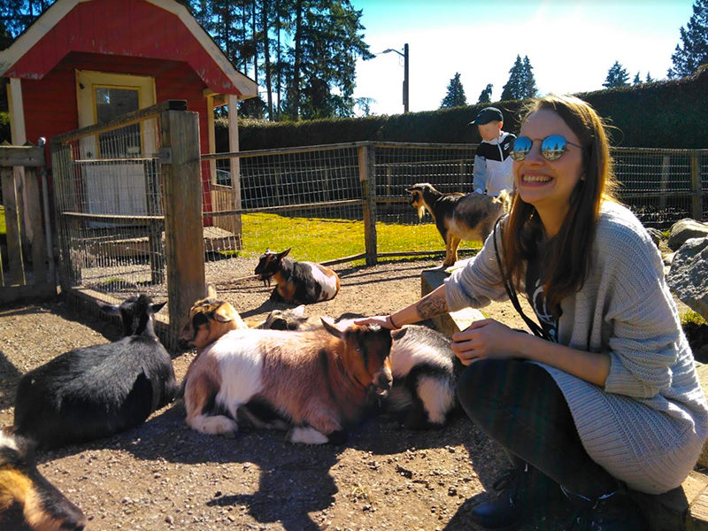 Lisa Matthias, Scholcommlab visiting scholar, crouches down to pet a baby goat at Maplewood Farm, North Vancouver