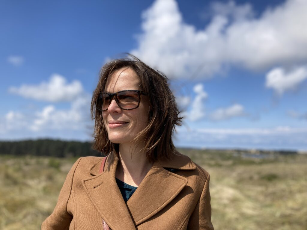 Kathleen Gregory wearing sunglasses against the blue cloudy sky of a brilliant, windy day