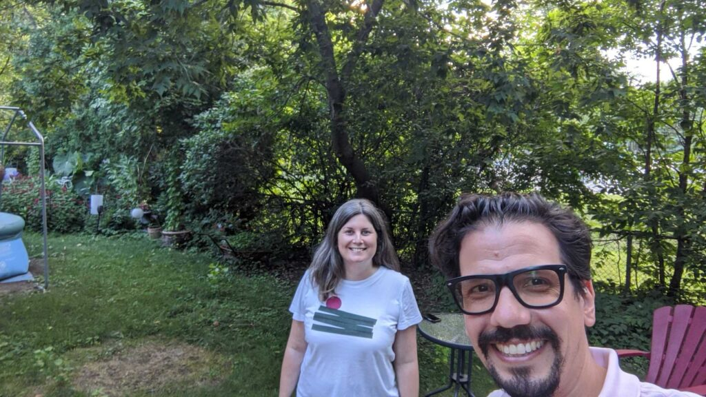 ScholCommLab co-directors Stefanie Haustein and Juan Pablo Alperin smile for the camera against a sunlit backdrop of trees.