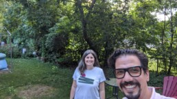Juan and Stefanie, scholarly communications lab co-directors, smile for the camera in a sunny backyard